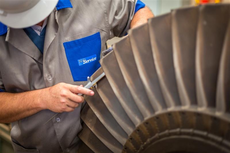 Homem realizando a manutenção de equipamento voltado à produção de energia.