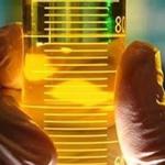 Mão segurando recipiente com biodiesel.