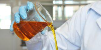 Mão derramando biodiesel de dentro de um Becker, recipiente químico utilizado em laboratórios.