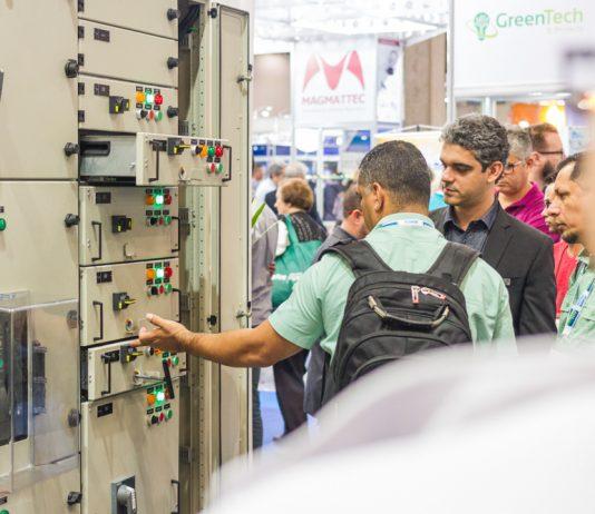 Homens observando painel elétrico com diversos botões.