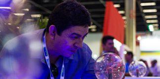 Homem observando esfera de plasma.
