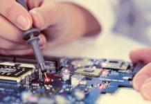 Mão de pessoa branca manuseia pequena solda em circuito de transmissão eletrônico