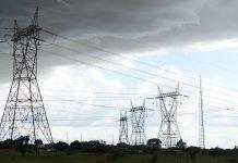 Torres de transmissão de energia elétrica vistas em dia de céu acinzentado, em referência ao megaleilão de transmissão