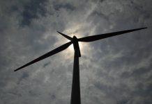 Sombra de torre de energia eólica é vista de baixo, com luz do sol ao fundo em dia cinza com nuvens